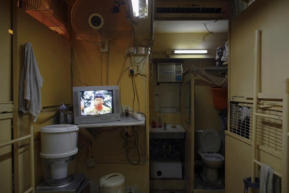 """Chiếc vô tuyến đặt ở khu vực hành lang chung giữa những """"hộp gỗ"""" – chỗ ở của mọi người. Để tối đa hóa thu nhập từ tiền thuê nhà ở khu trung tâm Hong Kong, chủ nhà thường xây dựng """"căn phòng quan tài"""" (coffin home)."""
