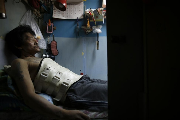 Ông Kam Chung, 49 tuổi, đeo nẹp ở bụng đang cố chợp mắt trong căn buồng gỗ của mình ở Hong Kong.
