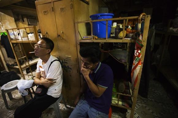 Hai người đàn ông ngồi xem tivi khu vực hành lang chung trong căn hộ quan tài họ thuê với giá 167 USD giữa lòng Hong Kong.