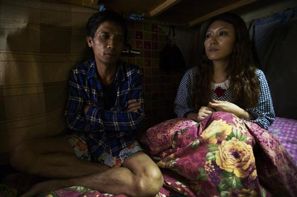 Huang Shaochang, 46 tuổi, và vợ Li Rong, 37 tuổi, ngồi trên giường bên trong căn hộ quan tài chỉ rộng 3,2m2.