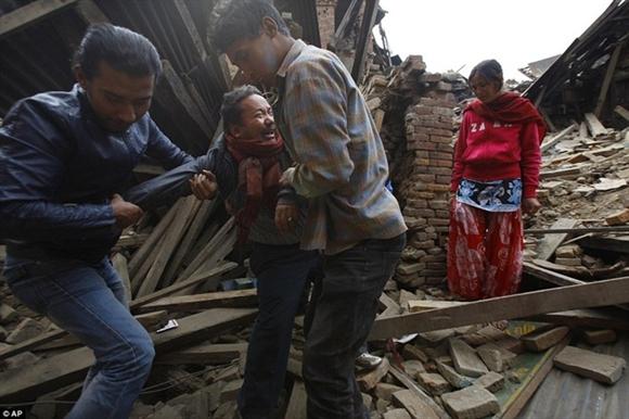 Người dân đưa một người đàn ông ra khỏi ngôi nhà đổ nát sau trận động đất. Tuy nhiên, mẹ của anh ta đã bị chôn vùi dưới những lớp gạch. Ảnh: AP