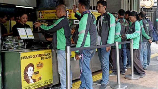 Các tài xế cho GrabFood xếp hàng để thu thập đơn đặt hàng tại một cửa hàng Pisang Goreng Bu Nanik ở Jakarta, Indonesia