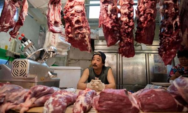 Một người bán thịt chờ khách hàng tại quầy hàng của anh ta ở chợ Bắc Kinh. Ảnh: Nicolas Asfouri