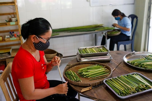 Workers make straws from grass at the 3T workshop in Long An province. Photo: Reuters