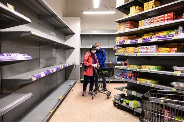 Những người mua sắm đeo khẩu trang bảo vệ đẩy xe của họ qua các kệ siêu thị với các kệ trống không tại Hồng Kông vào ngày 6/2/2020. Nguồn: Bloomberg