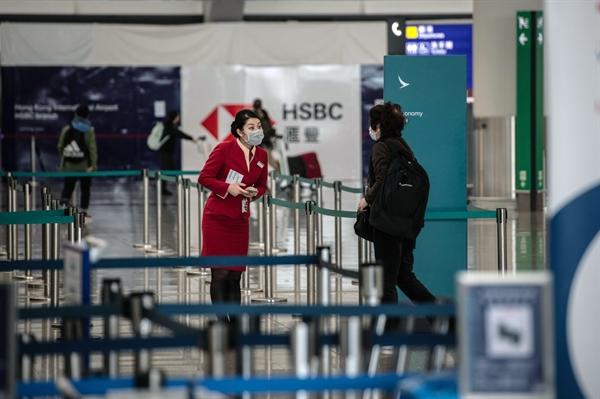 Một nhân viên của Cathay Pacific Airlines đeo mặt nạ bảo vệ nói chuyện với một hành khách tại sân bay quốc tế Hồng Kông vào ngày 6/2/2020. Nguồn: Bloomberg