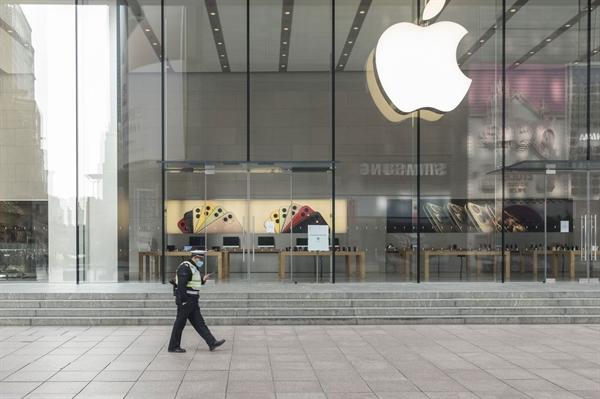 Một sĩ quan cảnh sát đeo khẩu trang bảo vệ đi ngang qua một cửa hàng Apple đã đóng cửa ở Thượng Hải vào ngày 05/02/2020. Nguồn: Bloomberg