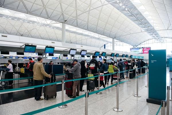 Khách du lịch đứng xếp hàng gần quầy làm thủ tục của Cathay Pacific Airways Ltd. tại Sân bay Quốc tế Hồng Kông vào ngày 10/3/2017. Nguồn: Bloomberg