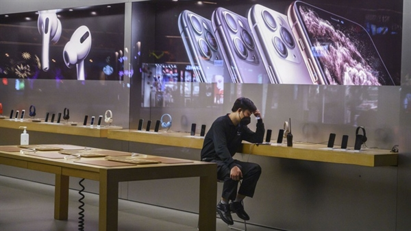 Một người ngồi tại cửa hàng của Apple. Nguồn: Internet