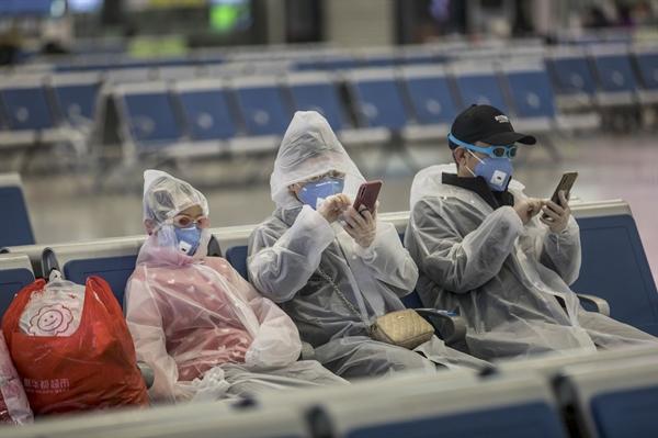Một gia đình đeo thiết bị bảo hộ toàn thân tại phòng chờ xe lửa ở Thượng Hải. Nguồn: Bloomberg