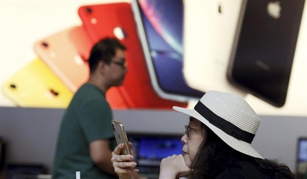 Một khách hàng nhìn chăm chú vào chiếc iPhone tại một cửa hàng của Apple ở Trung Quốc. Nguồn: SCMP