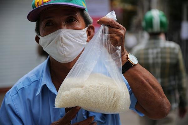 Nhiều người già cũng đến xếp hàng chờ lấy gạo. Bàn tay nhăn nheo cầm túi gạo, người đàn ông này cảm thấy yên tâm trong những ngày không đi làm chờ qua giai đoạn khi khăn.