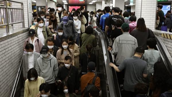Hành khách Hàn Quốc đeo mặt nạ bảo vệ khi họ đi trên thang cuốn và cầu thang sau khi xuống tàu điện ngầm trong giờ cao điểm vào ngày 11 tháng 5 năm 2020 tại Seoul, Hàn Quốc.
