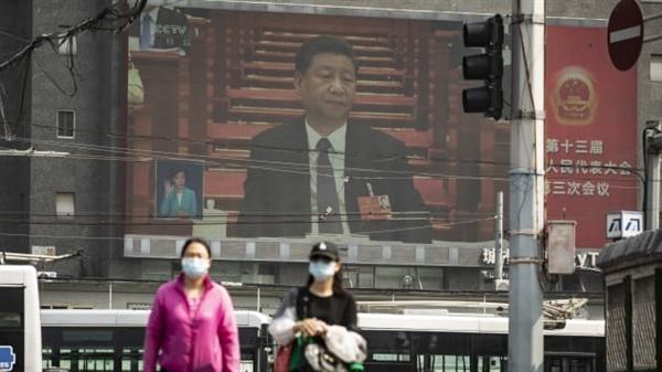 Người đi bộ đeo khẩu trang đi dọc theo đường phố phía trên là màn hình hiển thị chương trình phát sóng trực tiếp của Chủ tịch Trung Quốc Tập Cận Bình. Ảnh: Bloomberg