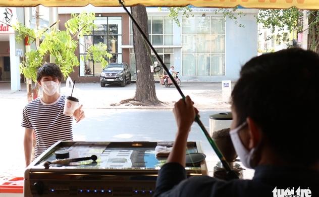 Saigon café uses fishing rod to practice social distancing